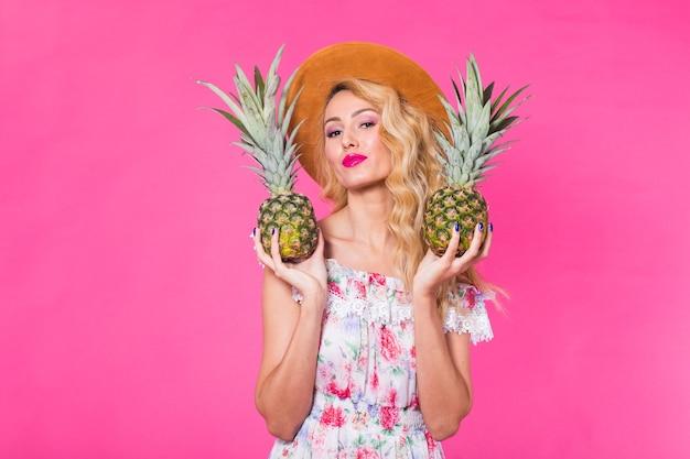 Porträt der glücklichen frau und der ananas über rosa hintergrund mit copyspace. sommer, ernährung und gesund