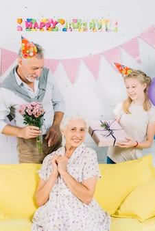 Porträt der glücklichen frau vor ehemann und enkelin mit geburtstagsgeschenken
