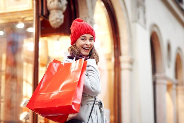 Porträt der glücklichen frau während des wintereinkaufs