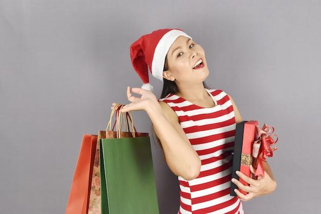Porträt der glücklichen frau weihnachtsmann-hut tragend und geschenkbox halten.