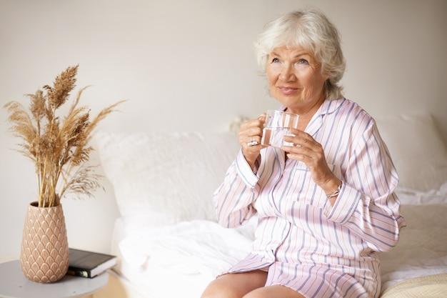 Porträt der glücklichen freudigen älteren frau, die gestreiften pyjamas sitzt, der auf rand des weißen betttrinkwassers vom glas sitzt und sorglosen gesichtsausdruck hat. morgenroutine, gesunde gewohnheiten und menschen