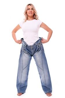 Porträt der glücklichen gealterten frau, die große jeans trägt