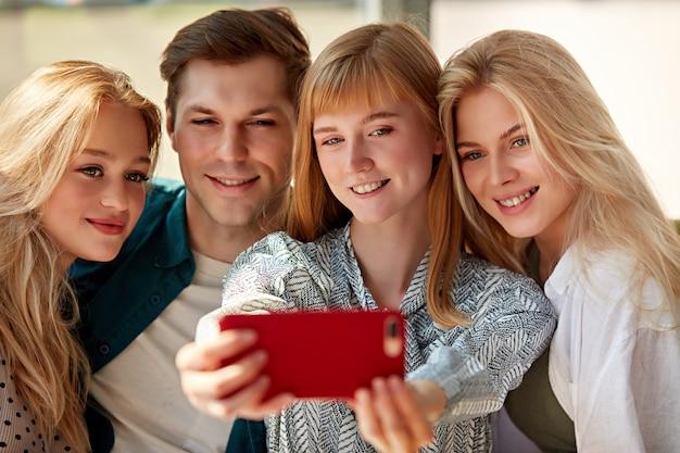 Porträt der glücklichen gruppe der jungen kaukasischen freunde, die foto machen