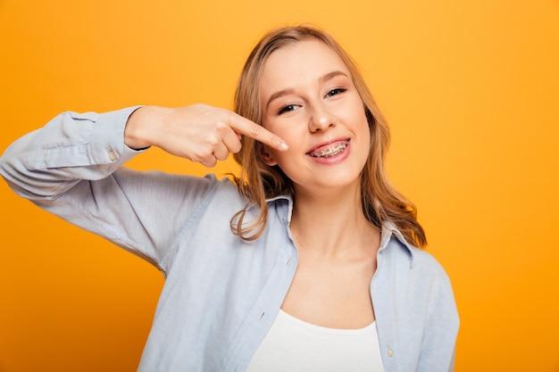 Porträt der glücklichen gütigen frau mit kastanienbraunem haar, das breit lächelt und zeigefinger auf zahnspangen auf ihren zähnen zeigt, lokalisiert über gelbem hintergrund