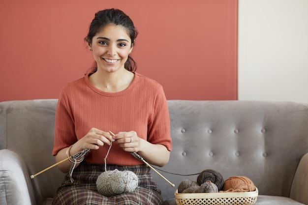 Porträt der glücklichen hausfrau, die vorne lächelt, während sie auf sofa im raum sitzt und mit nadeln strickt