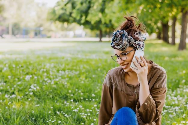 Porträt der glücklichen hippie-frau, die am telefon im freien spricht.