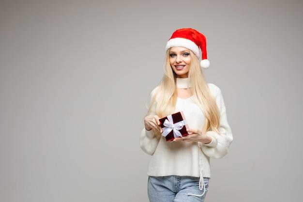 Porträt der glücklichen hübschen frau, die weihnachtsmannmütze trägt, während sie mit geschenk aufwirft, lokalisiert auf grau