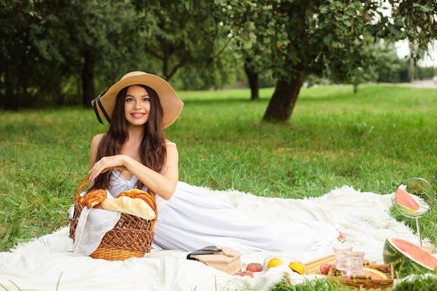 Porträt der glücklichen hübschen jungen dame im hut, die ruhe auf picknick im park hat, während sie einen korb brot in den händen hält