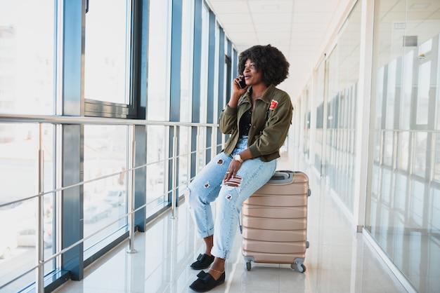 Porträt der glücklichen jungen afroamerikanerfrau, die auf koffer sitzt und mit handy am bahnhof spricht