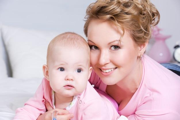 Porträt der glücklichen jungen aktiven mutter, die mit ihrem baby auf dem bett zu hause liegt