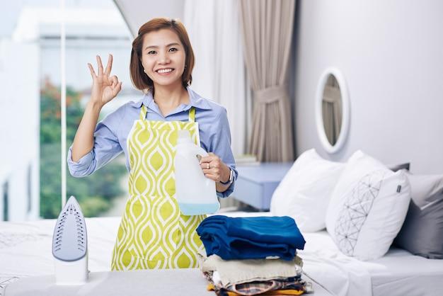 Porträt der glücklichen jungen asiatischen frau, die ok zeichen macht, wenn duftendes wasser in eisen hinzufügt