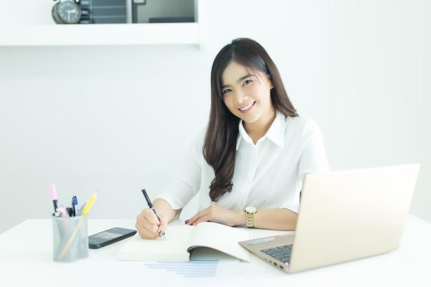Porträt der glücklichen jungen asiatischen geschäftsfrau, die kamera an ihrem arbeitsplatz betrachtet.