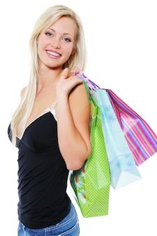 Porträt der glücklichen jungen blonden frau mit taschen der einkäufe über weiß
