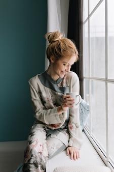 Porträt der glücklichen jungen blondine, die den morgen verbringt, der durch großes fenster mit tasse kaffee oder tee schaut und zu hause bleibt. türkisfarbene wand. tragen von seidenpyjamas in blumen, haare hoch.