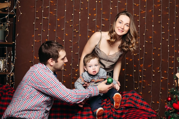 Porträt der glücklichen jungen familie, die zusammen auf bank während weihnachten im studio sitzt, posiert, lächelt und nach vorne schaut