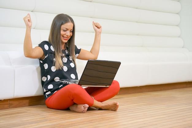 Porträt der glücklichen jungen frau, die auf dem boden mit den beinen gekreuzt sitzt und laptop verwendet. frau, die auf dem boden mit dem laptop betrachtet schirm sitzt.