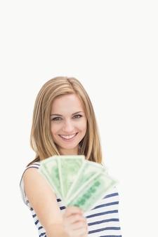 Porträt der glücklichen jungen frau, die aufgelockerte dollarbanknoten hält