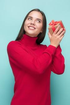 Porträt der glücklichen jungen frau, die ein geschenk lokalisiert auf blau hält