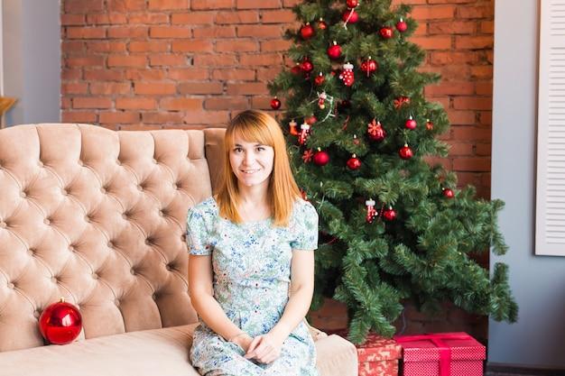 Porträt der glücklichen jungen frau, die nahe weihnachtsbaum entspannt