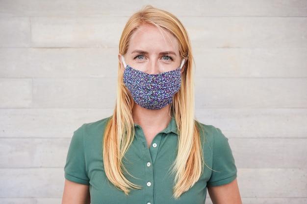 Porträt der glücklichen jungen frau, die schutzgesichtsmaske im freien trägt - fokus auf gesicht