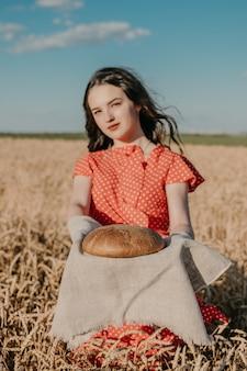 Porträt der glücklichen jungen frau im roten kleid, das rustikales roggenbrot auf weizenfeldsonnenhintergrund hält