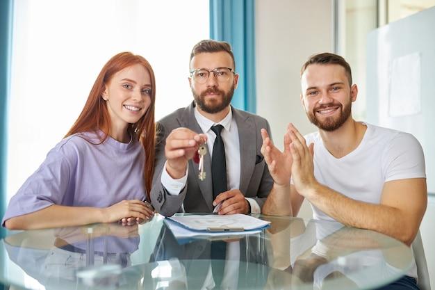 Porträt der glücklichen jungen frisch verheirateten familie mit immobilienmakler
