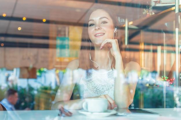 Porträt der glücklichen jungen geschäftsfrau mit becher in den händen kaffee am restaurant trinkend