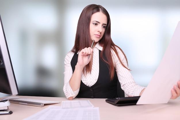 Porträt der glücklichen jungen geschäftsfrau sitting at desk-rechenfinanzierung