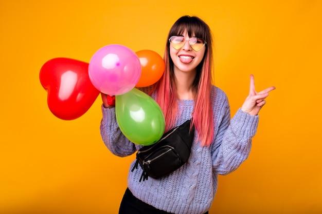 Porträt der glücklichen jungen hipsterfrau, die ok geste und lachen zeigt, blauer gemütlicher pullover, trendige brille und tasche, bunte luftballons halten, partystimmung.
