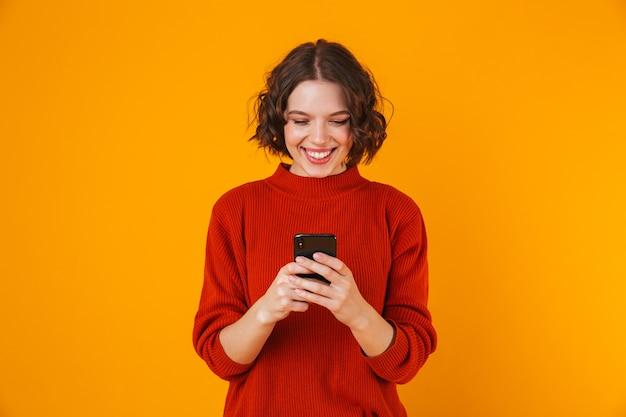 Porträt der glücklichen jungen hübschen frau, die lokal über gelbe wand unter verwendung des mobiltelefons aufwirft.