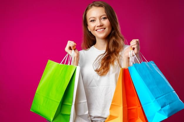 Porträt der glücklichen jungen lächelnden frau mit einkaufstüten