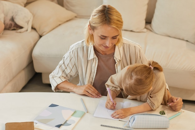 Porträt der glücklichen jungen mutter, die lächelt, während sie dem niedlichen kleinen mädchen hilft, das auf dem lernen zu hause zeichnet