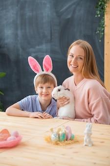 Porträt der glücklichen jungen mutter, die niedliches kaninchen hält und am tisch mit sohn im ohr kaninchen stirnband sitzt