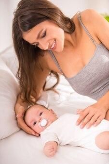 Porträt der glücklichen jungen mutter mit einem baby im bett.