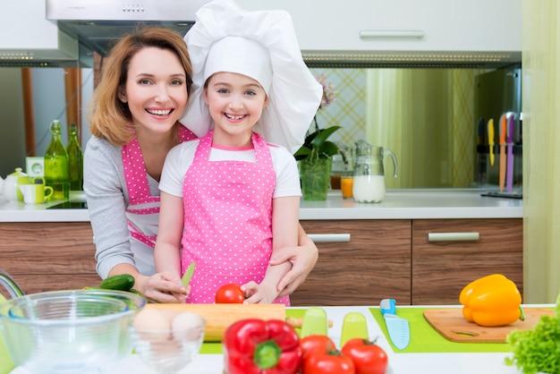 Porträt der glücklichen jungen mutter mit tochter in der rosa schürze, die an der küche kocht