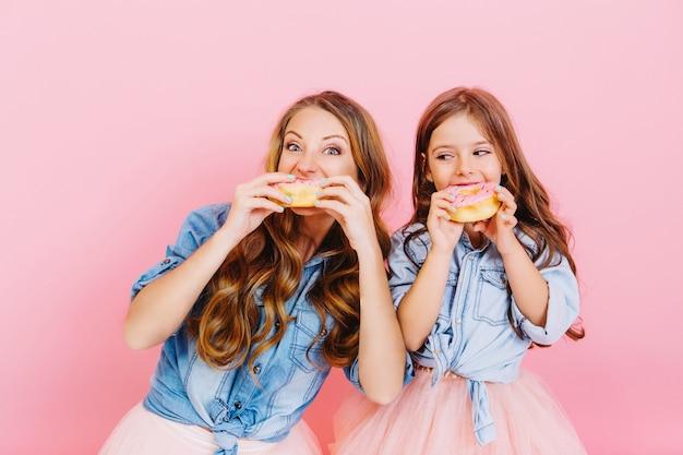 Porträt der glücklichen jungen mutter und der tochter, die leckere donuts nach dem abendessen essen, lokalisiert auf rosa hintergrund. zwei entzückende langhaarige lockige schwestern backten zusammen köstliche cupcakes und probierten sie.