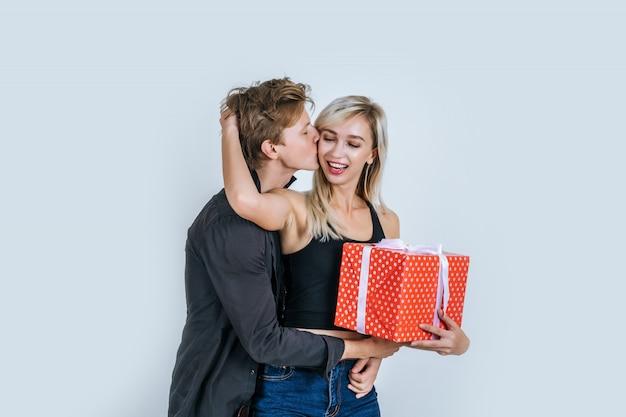 Porträt der glücklichen jungen paarliebe überraschen zusammen mit geschenkbox