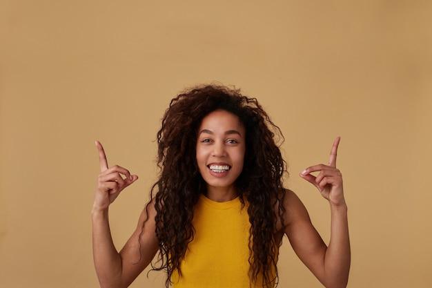Porträt der glücklichen jungen reizenden dunkelhaarigen lockigen brünetten frau mit natürlichem make-up, das zeigefinger erhöht hält, während sie nach oben zeigt und weit lächelt, lokalisiert auf beige