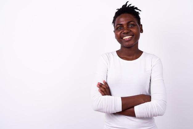 Porträt der glücklichen jungen schönen afrikanischen frau, die mit verschränkten armen lächelt