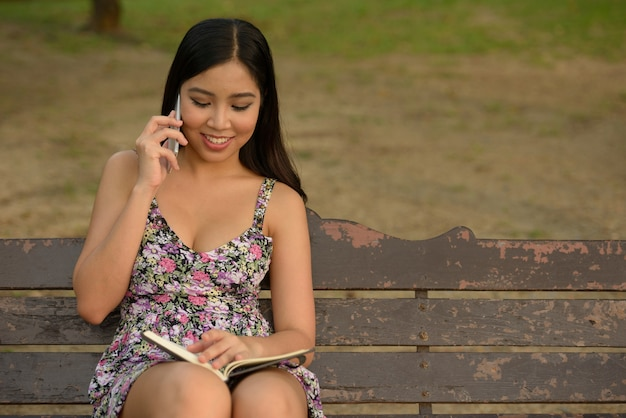 Porträt der glücklichen jungen schönen asiatischen frau, die am telefon am park spricht