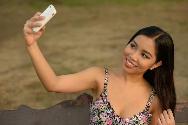 Porträt der glücklichen jungen schönen asiatischen frau, die selfie am park nimmt