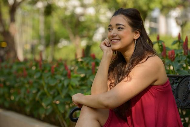 Porträt der glücklichen jungen schönen indischen frau, die am park denkt