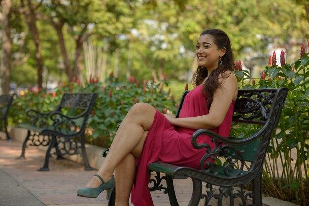 Porträt der glücklichen jungen schönen indischen frau, die am park sitzt