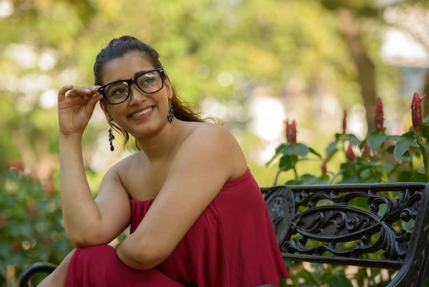 Porträt der glücklichen jungen schönen indischen frau, die brillen am park trägt