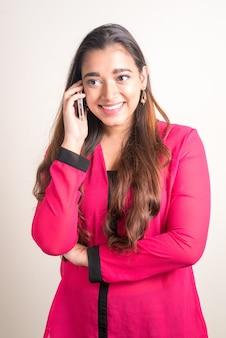 Porträt der glücklichen jungen schönen indischen geschäftsfrau, die am telefon spricht
