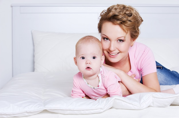 Porträt der glücklichen jungen schönen mutter, die mit ihrem baby auf dem bett liegt