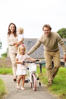 Porträt der glücklichen jungen vierköpfigen familie mit einem kleinen fahrrad gehend in den park