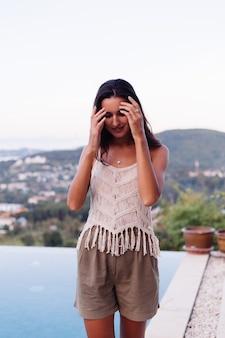 Porträt der glücklichen kaukasischen ruhigen romantischen frau im lässigen blick mit langen haaren, die ohrringe und halskette auf hintergrund erstaunlich schöne ansicht auf grünen bergen tragen