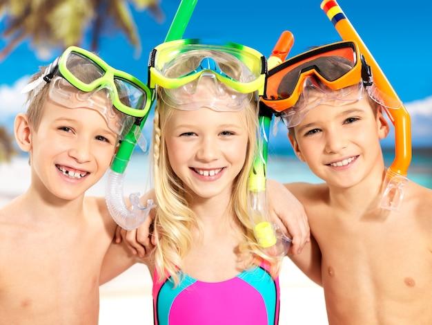 Porträt der glücklichen kinder, die am strand genießen