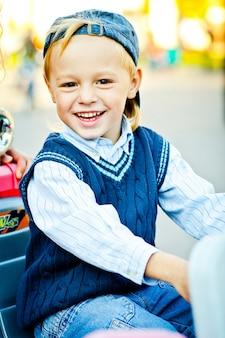 Porträt der glücklichen kindheit. stylischer kleiner junge im blauen hut, pullover und hemd
